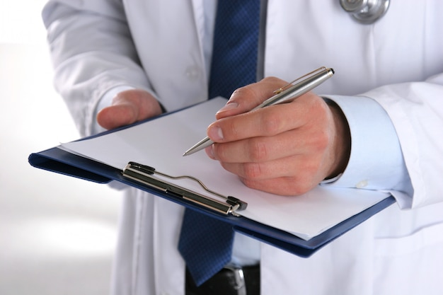 Male doctor standing with folder,