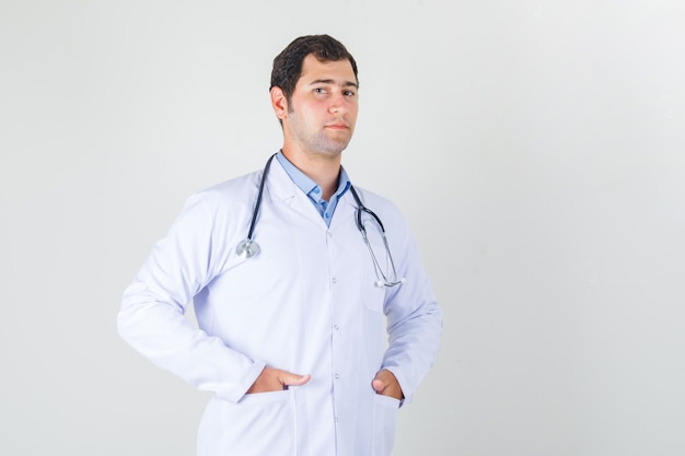Male doctor standing with hands in pockets in white coat and looking confident. front view.