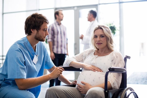 Male doctor talking to pregnant woman in wheelchair