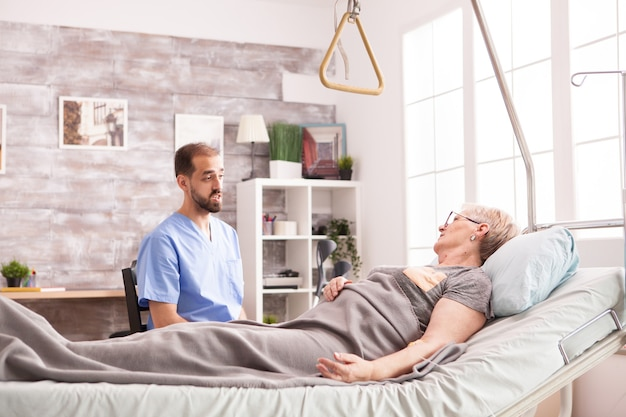 Male doctor talking with retired senior woman in nursing home lying in bed.