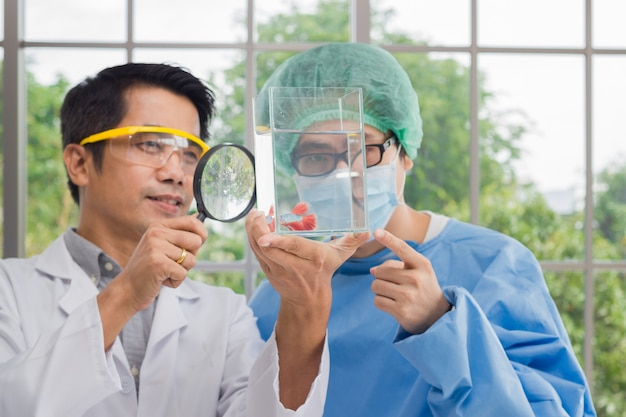 Мужской доктор команда держит рыба танк ищет борьбы рыбы через увеличительное стекло