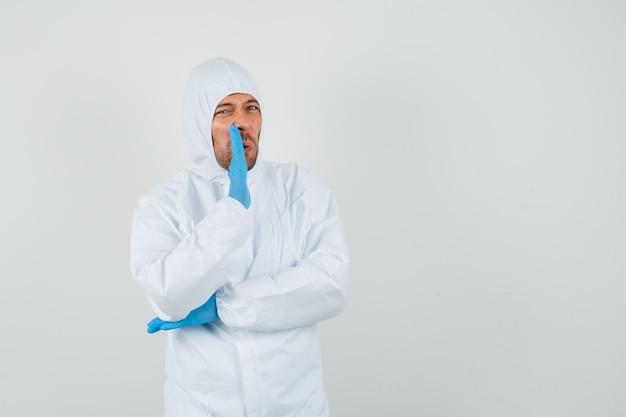 Medico maschio che dice segreto dietro la mano in tuta protettiva