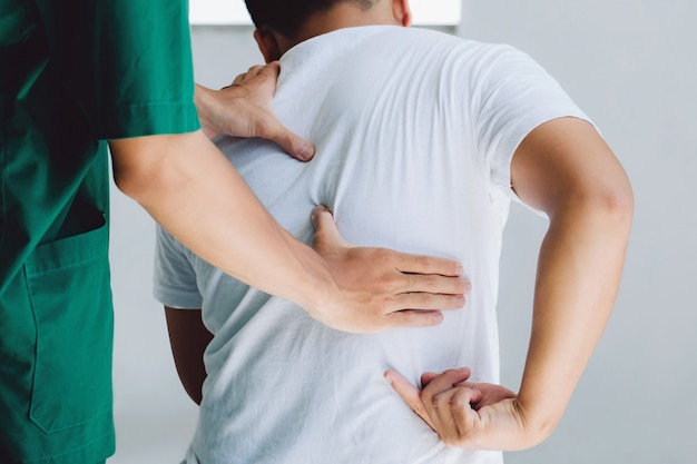 Male doctor therapist doing healing treatment on man's back.back pain patient, treatment, medical doctor,massage for back pain relief office syndrome