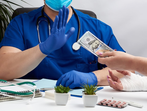 Male doctor in uniform and in blue latex medical gloves sits at a table and shows with his hand a gesture of stop
