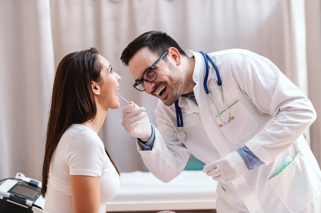 Male doctor in uniform and with stethoscope around neck taking swab out of patient's mouth.
