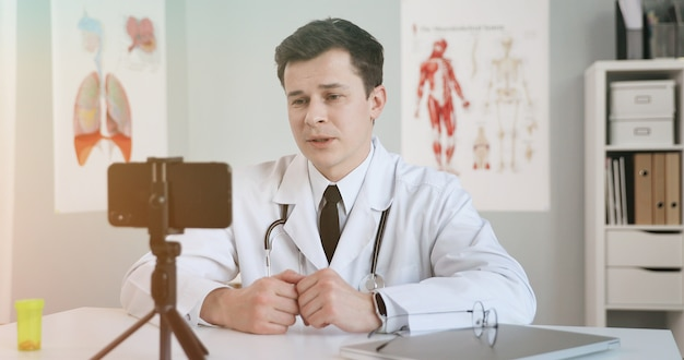 Male doctor using mobile phone for video conferencing