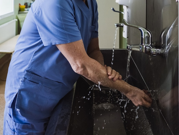 A male doctor washes his hands thoroughly with soap under running water in a stainless steel sink