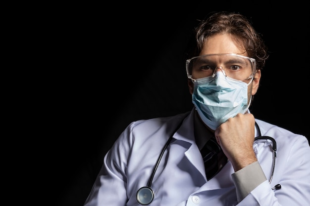 マスクとゴーグルを身に着けている男性医師は、黒い背景にcovid-19での作業にうんざりしています。