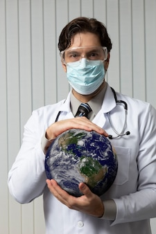Мужчина-врач в маске и очках с землей в руках, устал работать с covid-19 на белом фоне.