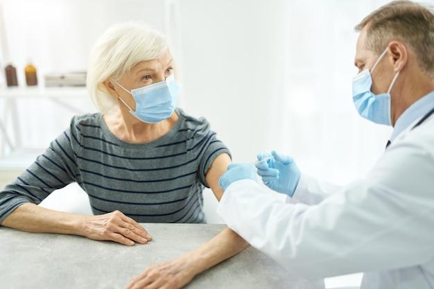 환자 팔에 주사를 하는 동안 보호용 안면 마스크와 멸균 장갑을 끼고 있는 남성 의사