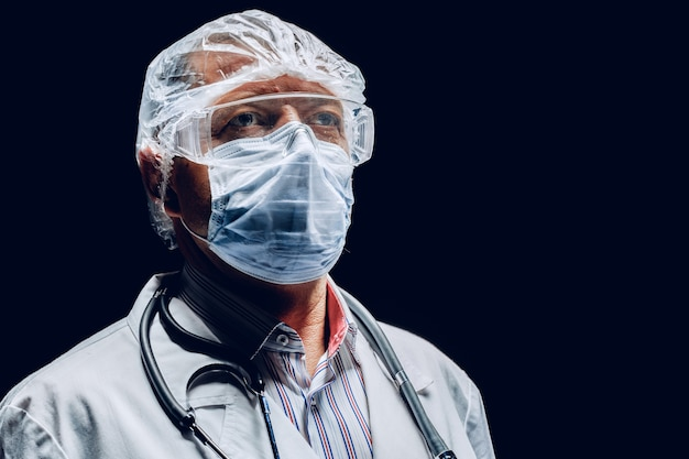 保護マスクとゴーグルを着用した男性医師。暗い背景。