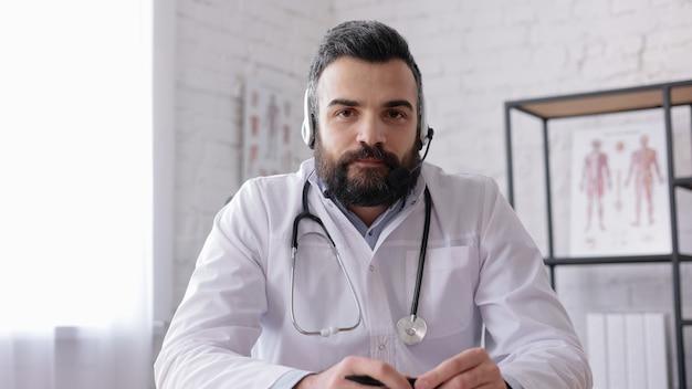 Врач-мужчина в белом халате консультирует пациента удаленно онлайн с помощью гарнитуры. вид с веб-камеры.