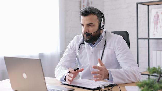 Врач-мужчина в белом халате имеет видеозвонок, видеочат, конференцию с коллегами или пациентом.