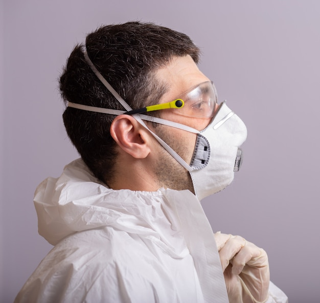 Male doctor wears a protective suit against bacterial and viral infection, covid 19, during a pandemic, glasses, mask for protection, rubber gloves.