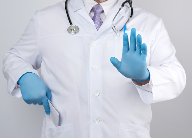 Male doctor in a white coat and blue sterile gloves shows a stop gesture with his hand