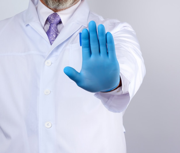 Male doctor in a white coat and blue sterile gloves shows a stop gesture with his right hand