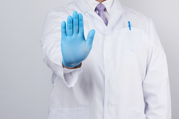Male doctor in a white coat and blue sterile gloves shows a stop gesture