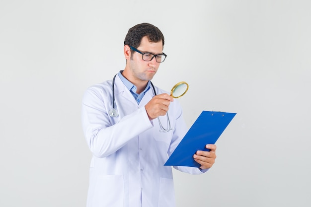 Male doctor in white coat, glasses holding magnifying glass over clipboard and looking busy