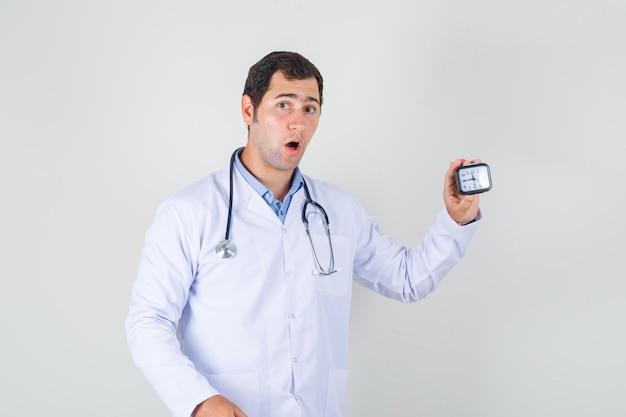 Medico maschio in camice bianco che tiene orologio e che sembra sorpreso
