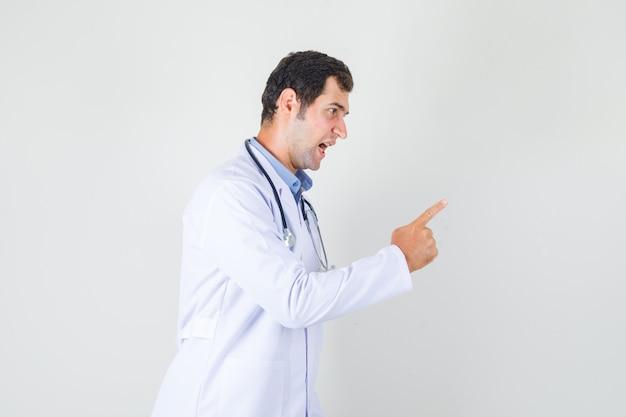 Medico maschio in camice bianco, gridando e avvertendo qualcuno e guardando nervoso.