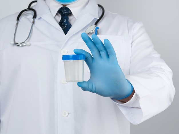 Male doctor in a white coat and tie stands and holds a plastic container for urine specimen