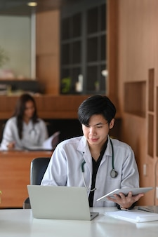 Male doctor in white uniform working with computer laptop in medical clinic office.