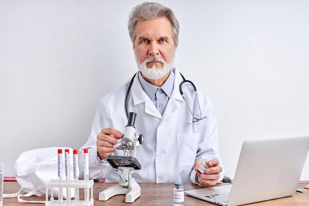 실험실에서 covid-19 및 노트북에 대한 혈액 샘플을 가진 남성 의사