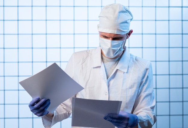 Male doctor with files on hospital holding clipboard and writing a prescription