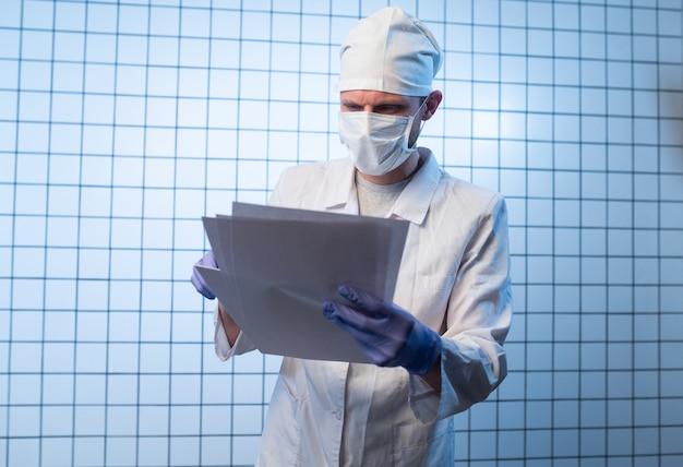 クリップボードを持ち、処方箋を書く病院のファイルを持つ男性医師