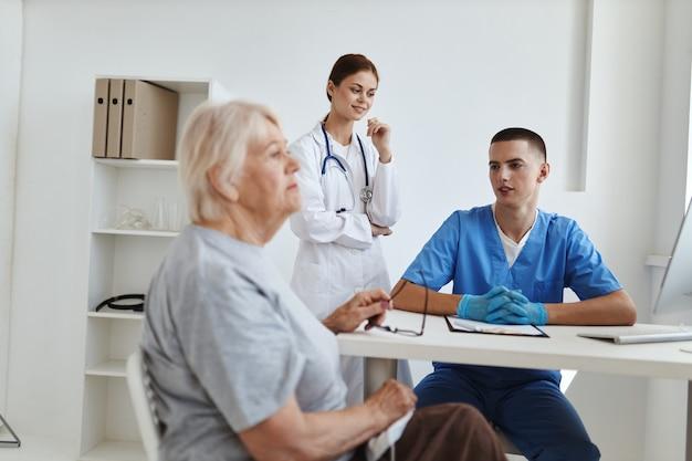 Male doctor with a nurse examining an elderly woman health hospital