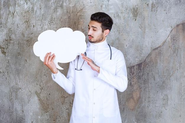 空白の雲の形の情報ボードを保持し、思慮深く見える聴診器を持つ男性医師。