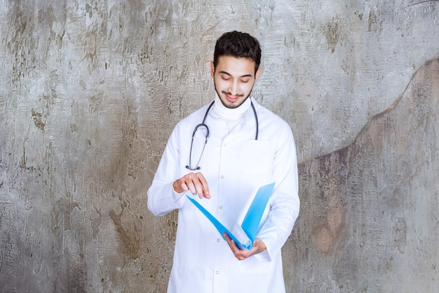 파란색 폴더를 들고 청진기를 가진 남자 의사