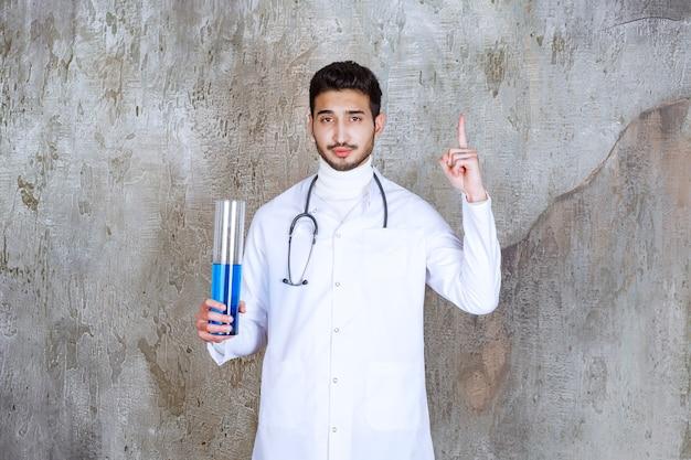 파란색 액체가 들어 있는 화학 플라스크를 들고 새로운 방법에 대해 생각하는 청진기를 가진 남성 의사