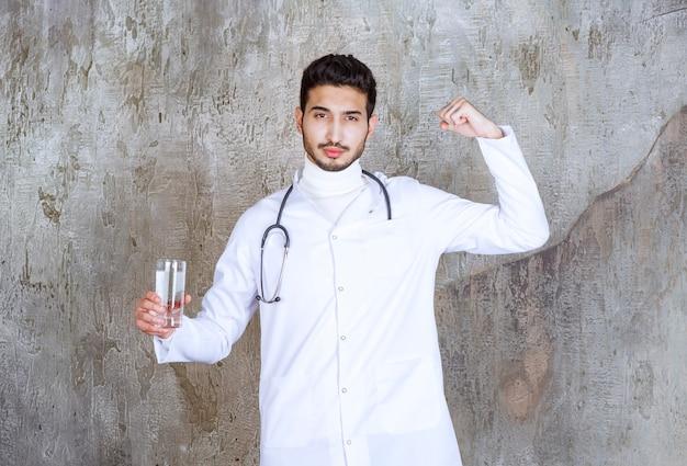 純粋な水のガラスを保持し、肯定的な手のサインを示す聴診器を持つ男性医師