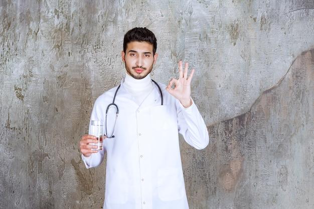 純粋な水のガラスを保持し、肯定的な手の兆候を示す聴診器を持つ男性医師