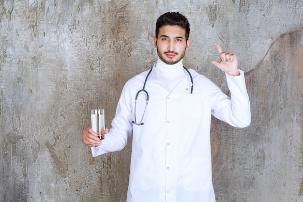 純粋な水のガラスを保持し、量を示す聴診器を持つ男性医師。