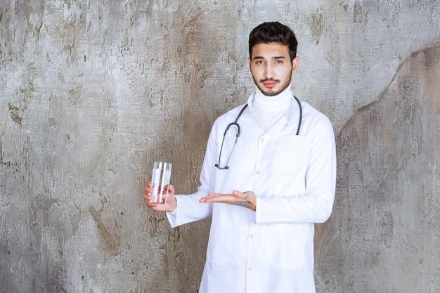 純粋な水のガラスを保持している聴診器を持つ男性医師。