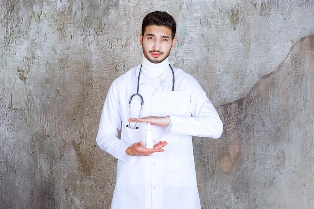청진 기 흰 손 소독제 병을 들고 남성 의사.