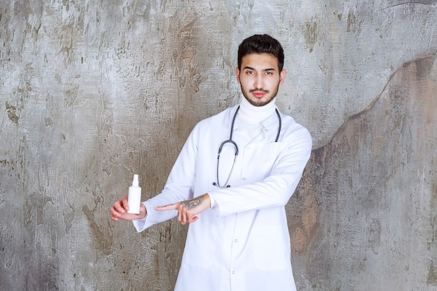 白い手の消毒剤のボトルを保持している聴診器を持つ男性医師。