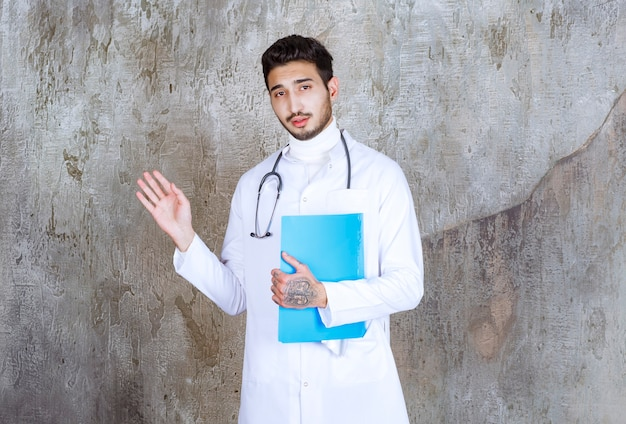 Male doctor with stethoscope holding a blue folder and interacting with the person around.
