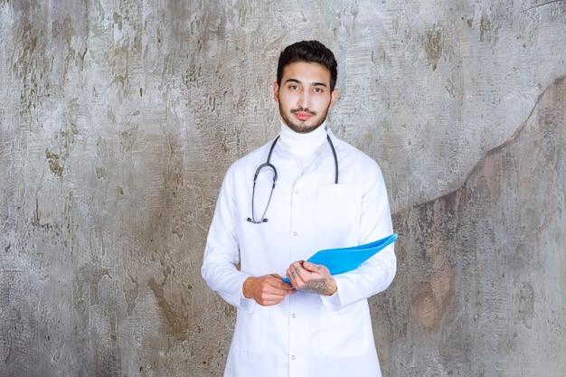 Medico maschio con lo stetoscopio che tiene una cartella blu