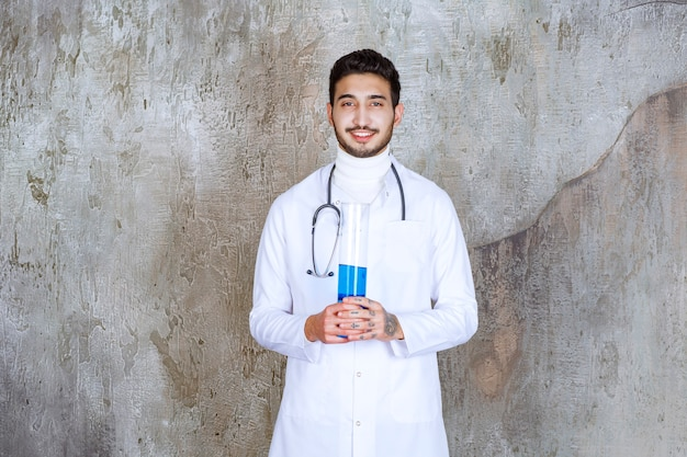Male doctor with stethoscope holding a chemical flask with blue liquid inside