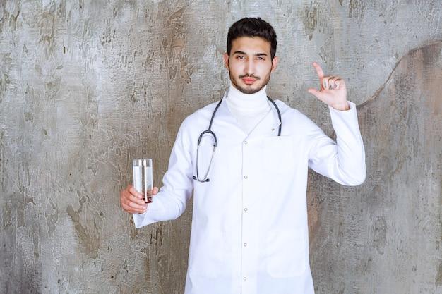 Medico maschio con lo stetoscopio che tiene un bicchiere di acqua pura e mostra la quantità.