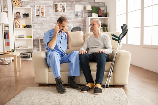 Male doctor with stethoscope in nursing home to check old man heart.