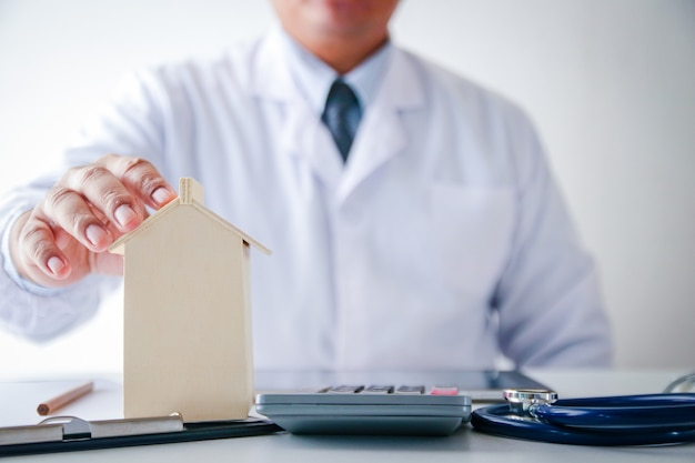 The male doctor wore a white dress, holding a toy house on the table. real estate care concept