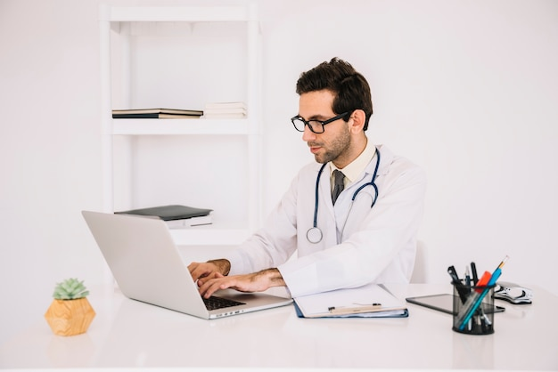 Male doctor working on laptop