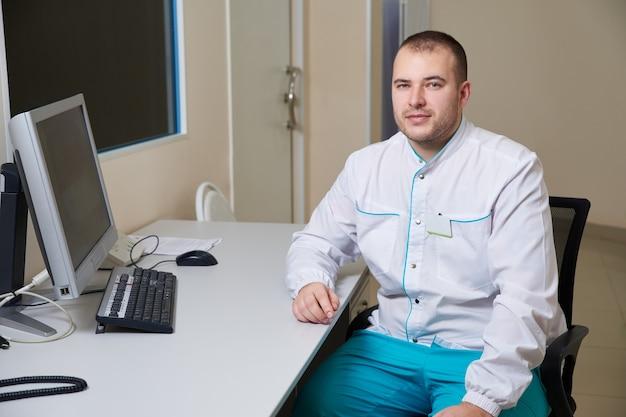 Мужчина-врач, работающий на компьютере в медицинской клинике