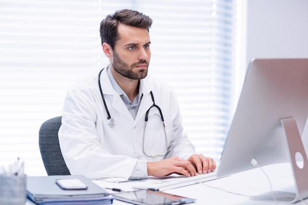 Мужской доктор работает на персональном компьютере