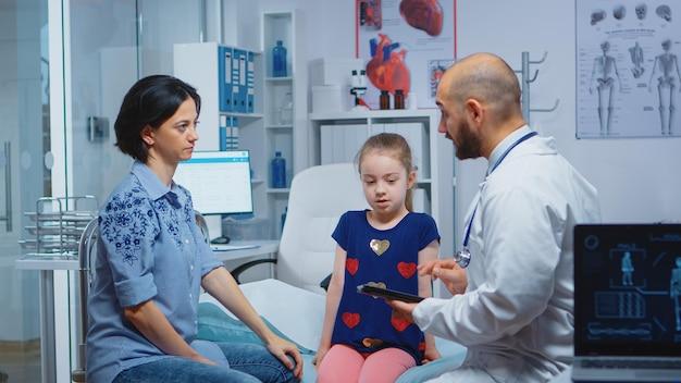 女性と話しているタブレットで子供の診断を書く男性医師。病院で医療サービス相談治療を提供する医学の医療従事者医師の専門家