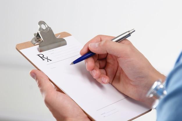 Male doctor writing prescription on clipboard